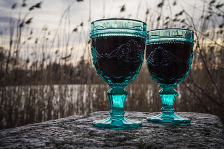 red wine glasses on a lake at sunset time