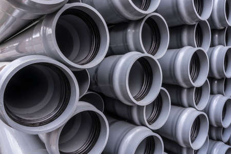 Stack of plastic pipes on a construction site.