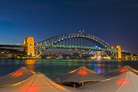 quayside: Sydney Harbour Bridge viewed from Circular Quay from behind lighted umbrellas