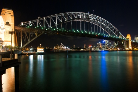 Sydney Harbour Bridge By Night with sparkling water reflection. The Sydney Opera House is at the background.