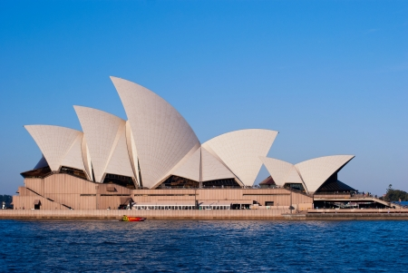 Sydney Opera House on blue sky background, blue water surface