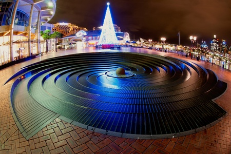 Christmas time in Darling Harbour, Sydney, Australia. Blue christmas tree in front of a rounded fountain. Stock Photo