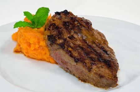Beefsteak with sweet potato on white dish isolated on white background