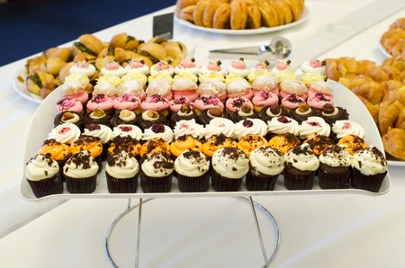 A tray of variety of colourful cupcakes for catering