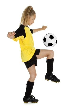 ropa deportiva: A la vista lateral de longitud ni�a de ocho a�os con el bal�n de f�tbol, ??aisladas sobre fondo blanco