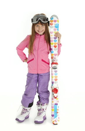 Full length photo of little girl dressed in ski wear holding colorful skis, standing on white background