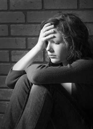 Teenage girl siiting against brick wall in a depressed state photo