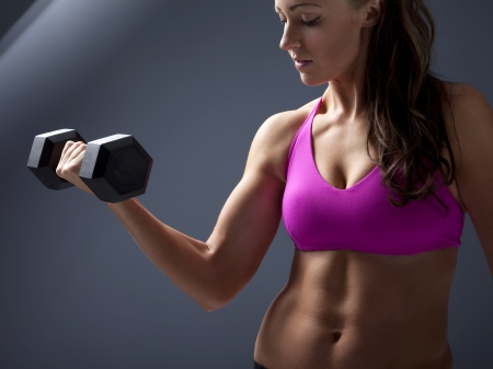 Studio photo of attractive young woman lifting dumbbell