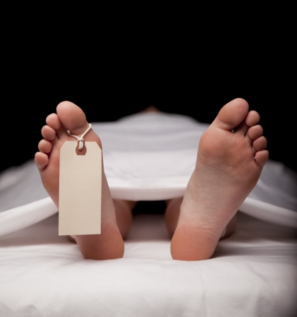 Deceased person covered in a sheet with a blank toe tag