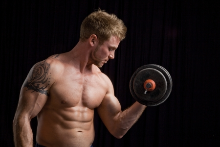 Studio photo of young man lifting weights against black background  photo