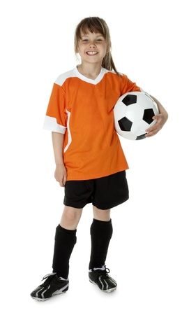 Seven year old girl holding soccer ball on white