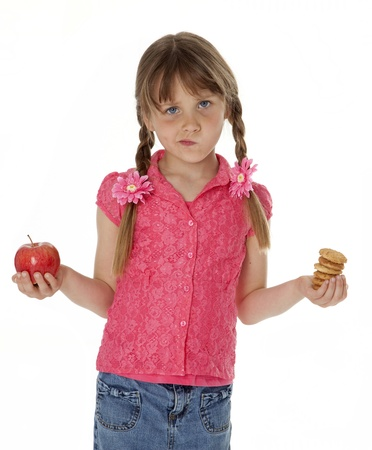 7 year old girl: 7 year old girl standing, holding apple in one hand, cookies in the other. White background.