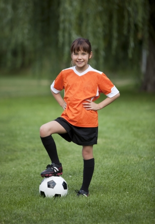 Full length photo of young girl standing with foot on soccer ball. photo