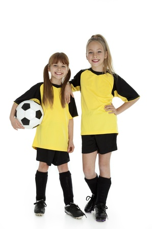 soccer uniforms: Full length front view of two young girls in soccer uniforms, holding soccer ball on white. Stock Photo