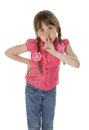 sneer: Angry little girl with finger on lips, on white background.