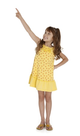 Full length photo of little wearing yellow summer dress pointing upward, on white background. Stock Photo