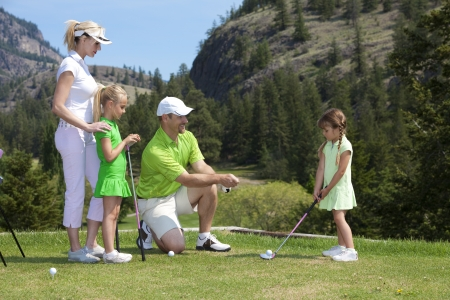 instructing: Outdoor photo of young family of four on golf course, father is instructing child. Stock Photo