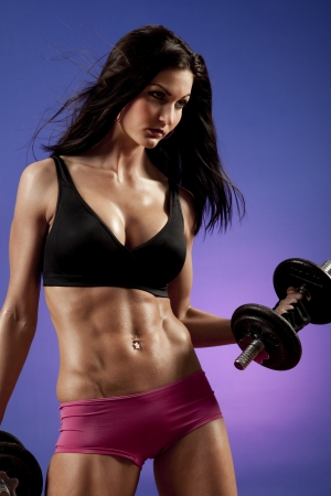 tummy: Studio photo of attractive female bodybuilder working out.