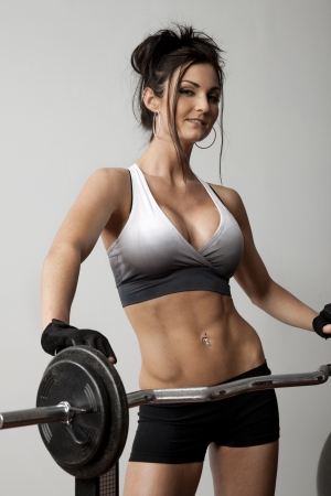 Attractive young fitness woman standing with barbell. photo