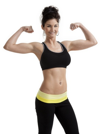 Young woman flexing her arm muscles, dressed in fitness clothing, shot on white background.