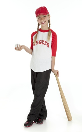 young girl dressed in baseball clothes, holding ball, leaning on bat