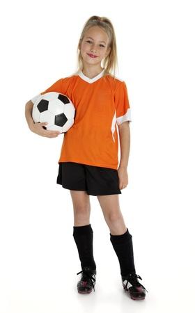 Negen jaar oud meisje met voetbal geïsoleerd op wit.