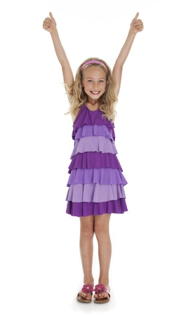 arm extended: Pretty seven year old girl with arms extended overhead giving thumbs up gesture on white background. Stock Photo