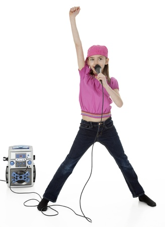 Full length studio photo of young girl holding microphone in front of karaoke machine, on white background  版權商用圖片