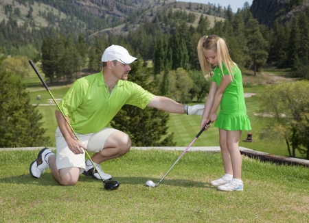 or instruction: Full length view of father and giving young daughter golf lesson.
