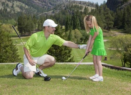 squatting: Visi�n integral de padre y dando lecciones de golf joven hija.