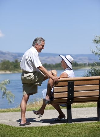 Seniors couple in rural outdoor setting looking at each other, conversing. photo