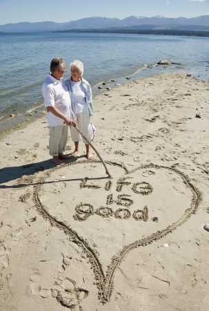 Happy retired couple on beach writing with stick in the sand.