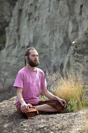 Young man meditating in outdoor spiritual setting.