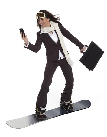 Attractive woman wearing business suit, carrying briefcase and cell phone, riding a snowboard on white background.