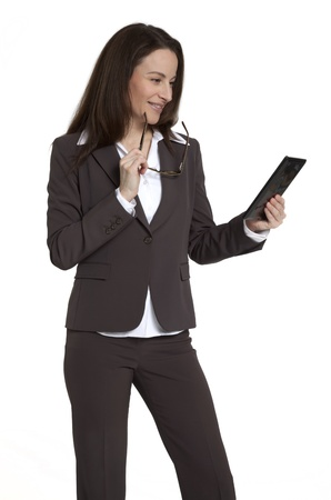 Attractive businesswoman holding and looking at tablet device against white background.