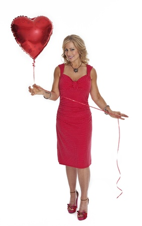 Full length photo of 40 year old woman in red dress holding heart shaped red balloon on white background. photo
