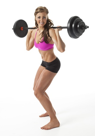 Attractive young woman standing with barbell on shoulders against white background. photo