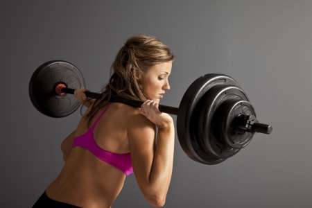 Attractive young woman with barbells on shoulder photo