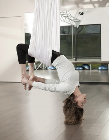 Woman doing anti gravity yoga exercise in fitness centre. Stock Photo - 19203363