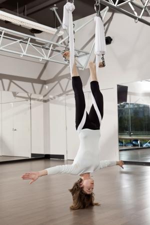 gravedad: Mujer haciendo ejercicio de yoga antigravedad en el gimnasio. Foto de archivo