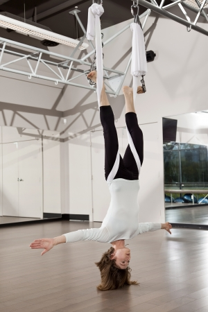 hang body: Woman doing anti gravity yoga exercise in fitness centre. Stock Photo