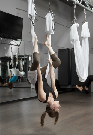 Woman doing anti-gravity exercise in fitness centre.
