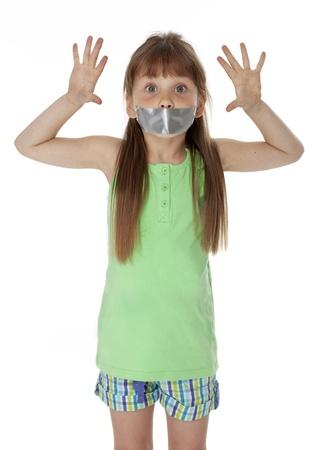 boca cerrada: Niña de pie, con la boca cubierta con cinta adhesiva, sobre fondo blanco.