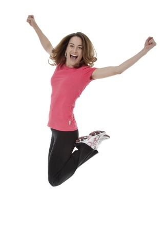 enthusiasm: Full length studio photo of attractive woman jumping in air with arms extended. White background. Stock Photo