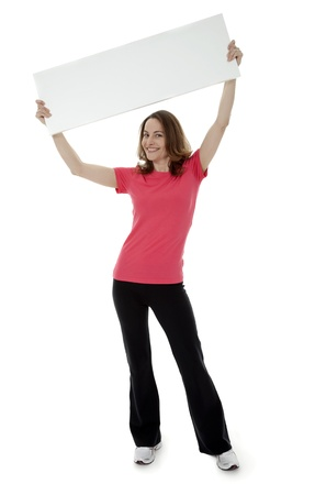 Full length view of pretty brunette woman holding blank sign overhead on white background.