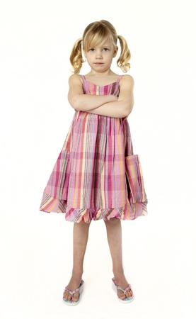 Full length studio photo of 5 year old girl with arms crossed, looking defiantly at camera. 版權商用圖片
