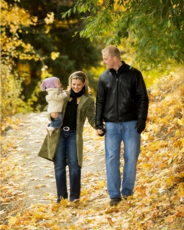 Young adult couple with baby, walking in autumn scene