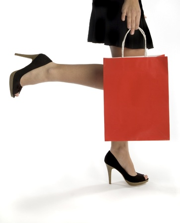 Waist-down view of woman carrying red shopping bag 版權商用圖片