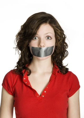 Studio photo of teenage girl with mouth taped closed on white background.