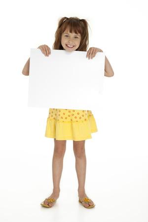 kids dress: Full length front view of cute little girl holding blank sign on white background  Stock Photo